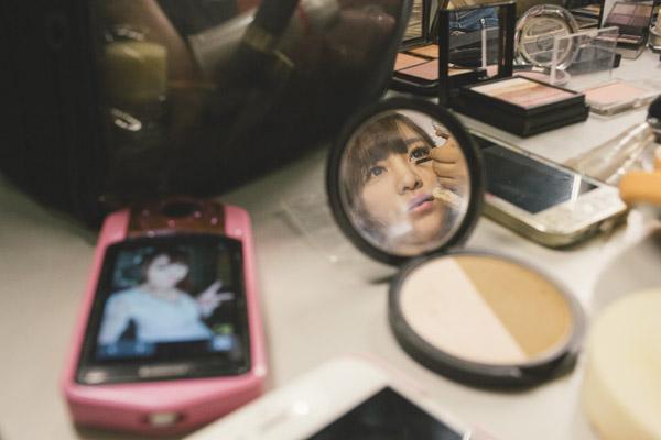 """网红""""王玥晨在录节目前化妆,一个被称之为""""美颜相机""""的数码相机摆放在化妆台上。这是不少网络红人的""""标配""""。"""
